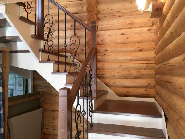 Деревянная лестница с коваными ограждениями на второй этаж